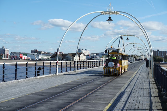 a yellow tram on a wooden seaside pier