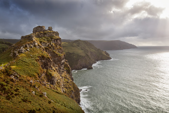 Castle rock bathed in warm sunlight under stormy clouds in Exmoor by Martyn Ferry Photography