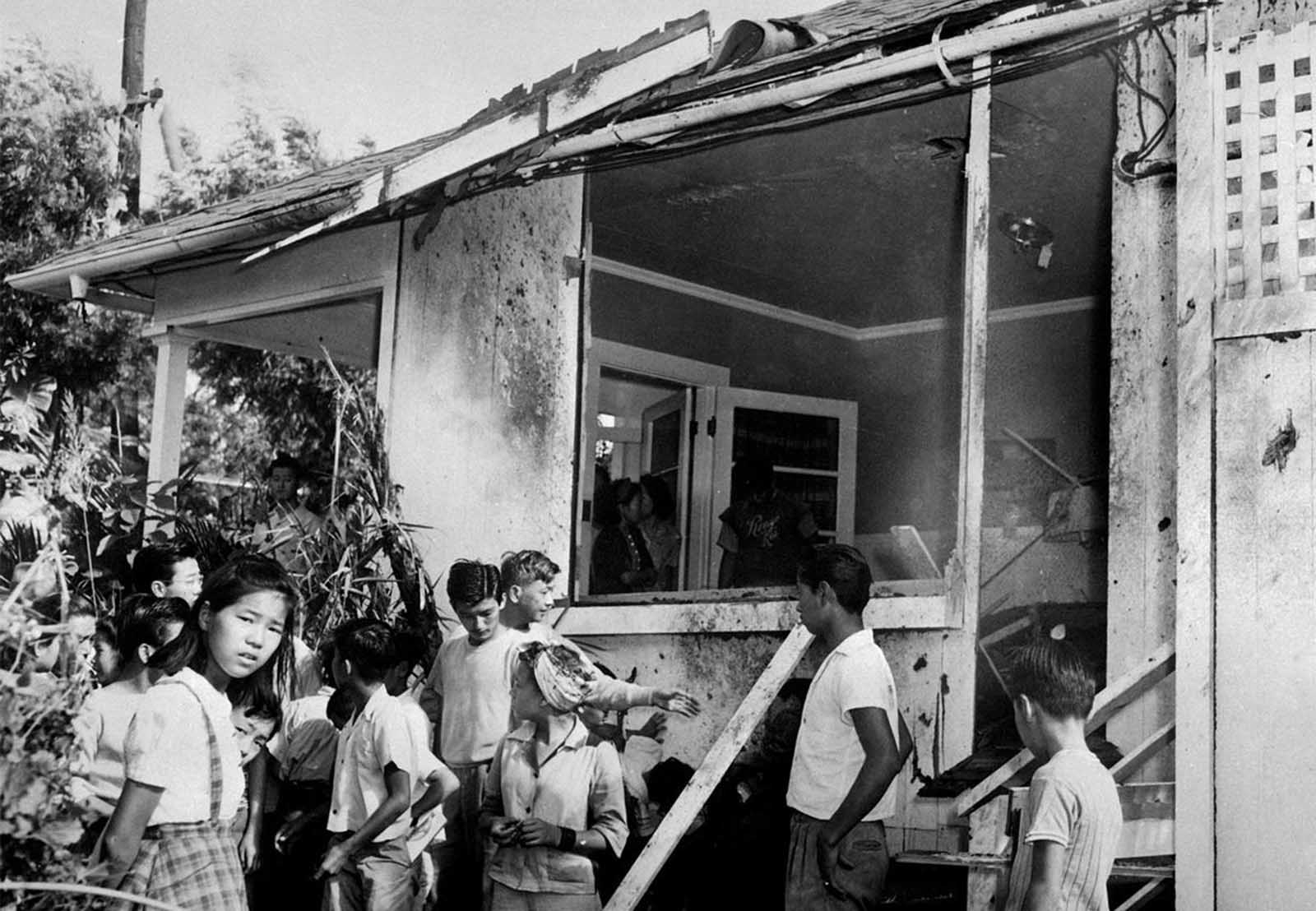 A small crowd inspects the damage, both inside and outside, after a Japanese bomb hit the residence of Paul Goo during the Japanese air raid on December 7, 1941.