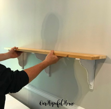 man holding distressed corbel DIY shelf