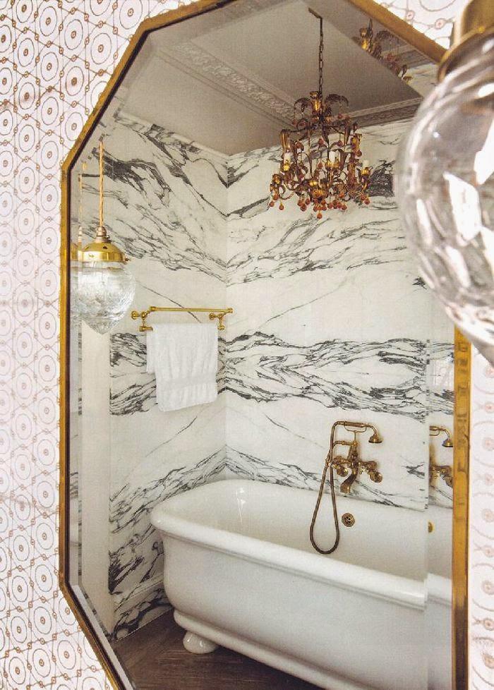 Bathroom walls witn marble, brass towel rack and white freestanding tub