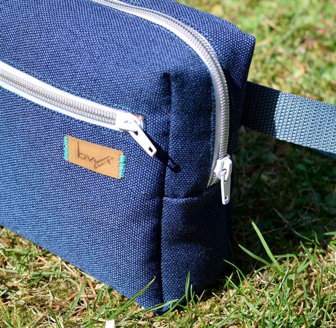 Nahaufnahme der Tasche: eckige Form der Tasche, metallisierte Reißverschlüsse und mein Buntwolf Label