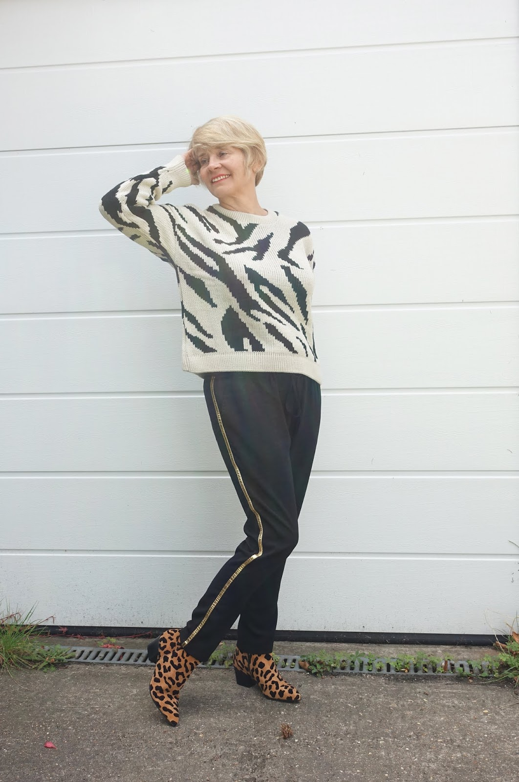 Leopard print ankle boots worn with a baggy zebra print jumper and black trousers
