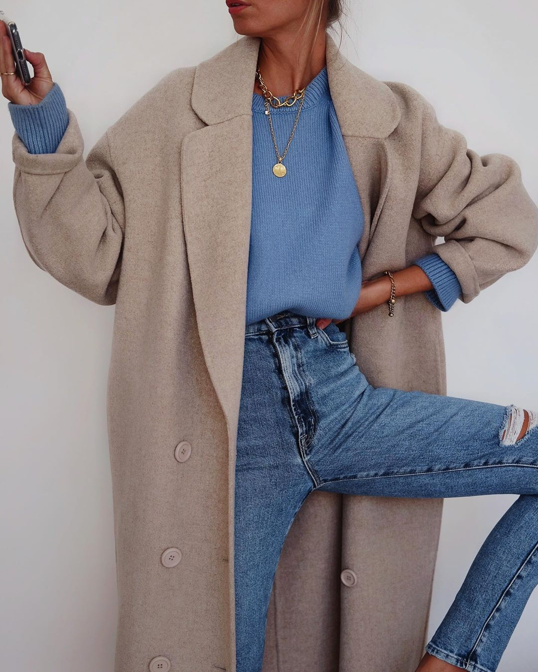 Casual-Cool Instagram Outfit — Andi Csinger in a beige coat, blue sweater, chain and coin pendant necklaces, and high-waisted jeans