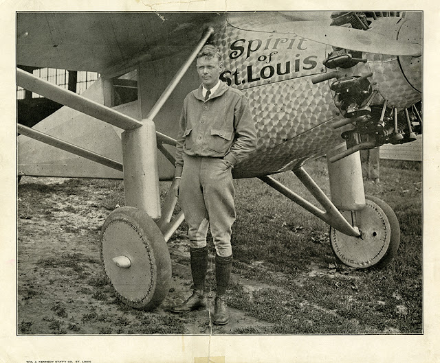 Charles Lindbergh, in flight gear, stands with his right hand in his pocket, next to the Spirit of St. Louis. 31 May 1927