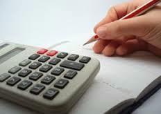 Calculadora y mano haciendo apuntes en un cuaderno
