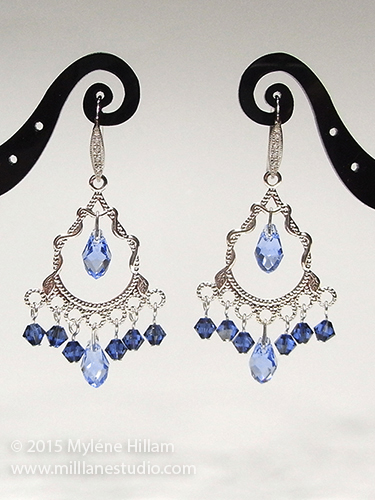 Silver filigree chandelier earrings with dangling blue crystals