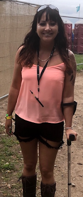 A caucasian woman with dark hair wearing a brightly coloured top stood leaning on a crutch.