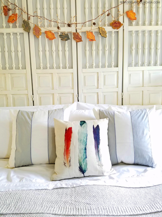warm blanket and white bedding with colorful feather pillow cover