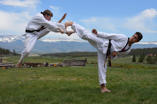 Martial arts black belts doing a side kick and jump front kick