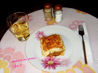 Μια βερσιον του μουσακα πιο ελαφρια και διπλα στο πιατο ποτηρι ασπρο κρασι χαμηλο και αλατιερα πιπεριαερα,πανω σε ροζ τραπεζομαντηλο με πιο σκουρα ροζ λουλουδια