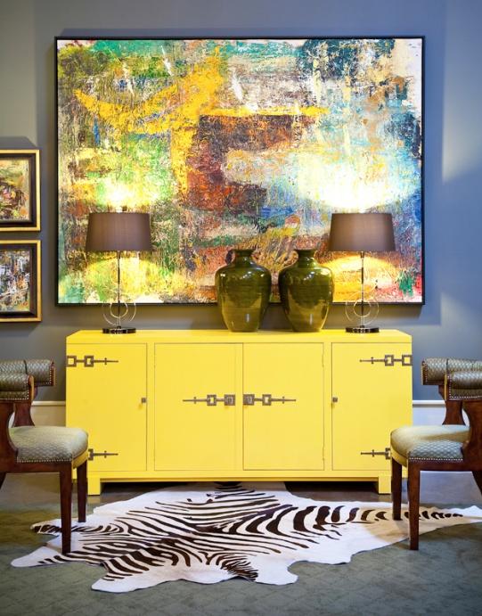 photographie d'un sejour avec enfilade jaune et tableau de peinture au mur et tapis zebré