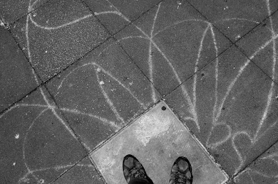 A photo looking down at my feet, with squiggly chalk lines coming out from them