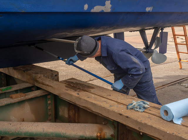 Photo of Phil applying antifoul paint to Ravensdale's hull