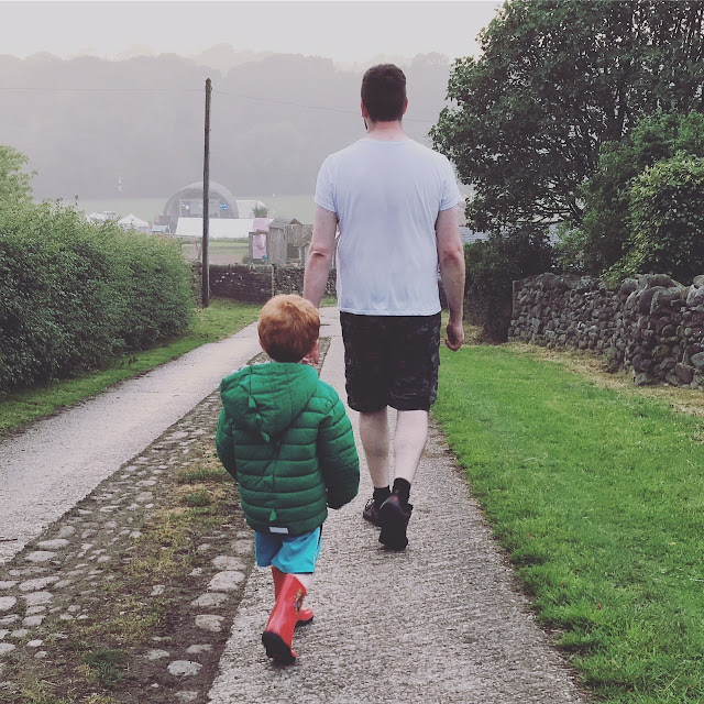 Father and son walking down a path to a field