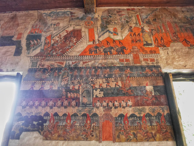 orange Buddhist temple murals in Luang Prabang
