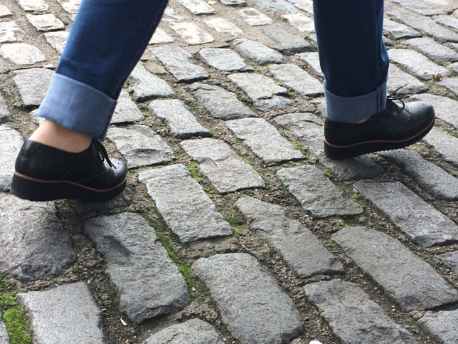 Un pamplonés, paseando sobre adoquines en mocasines saltarines con la piel de dos mastines