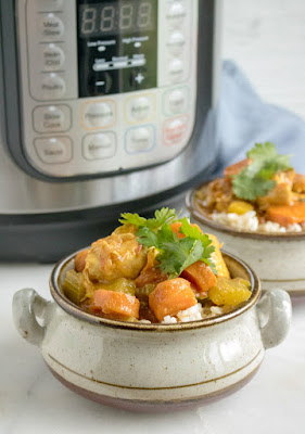 served chicken and veggie curry in front of pressure cooker
