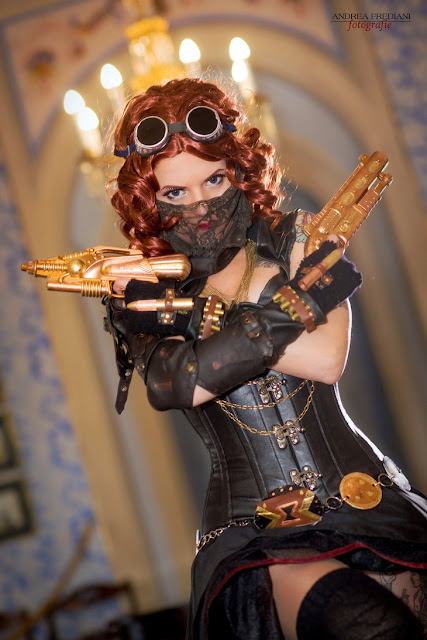 Woman dressed as Marvel superhero Black Widow in steampunk clothing (corset, skirt, goggles, guns, lace mask)