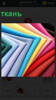 Текстильное полотно, ткань разного цвета аккуратно сложено на полке по цветовой гамме