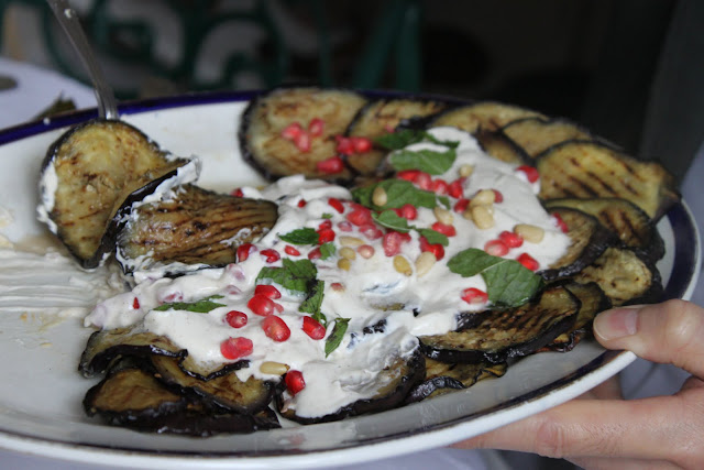 Grilled aubergine slices served with yoghurt, pine nuts and pomegranate seeds