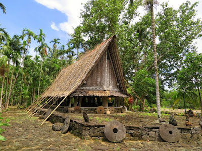 Traditional Yap house with stone money, Micronesia.
