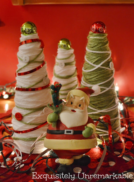 Christmas yarn trees with Santa figure standing in front of them
