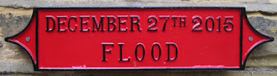 "Red oblong metal plaque, reads ""December 27th 2015 Flood"""