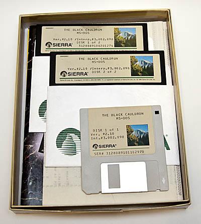 Dentro de una caja abierta se pueden ver varios disquetes de la aventura The Black Cauldron.