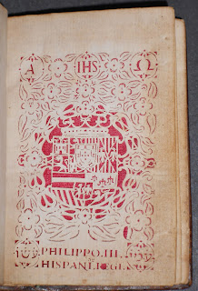 An elaborately decorated title page. The designs and letters are cut out of the page and show the red silk set behind it.