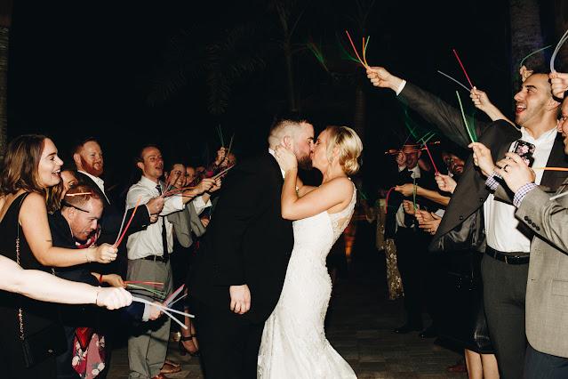 Last kiss before reception departure; sparkler send off