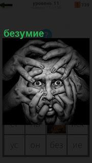 Лицо человека накрыли руками, которое выражает безумие