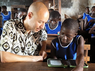 Ghana student reading with Worldreader CoFounder David Risher