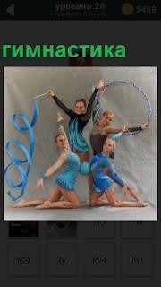 Четыре девушки занимаются гимнастикой, держа в руках спортивные ленточки и мячик между ними