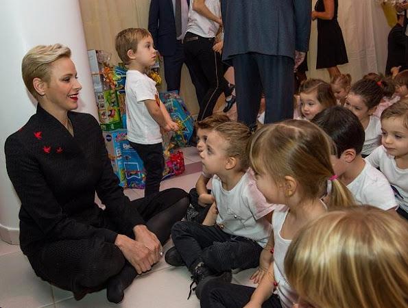 Prince Albert and Princess Charlene visited the kindergarten of Red Cross, children new year gifts. Princess Charlene Valentino dress