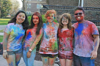 5smiling individuals are posing and their clothes are covered in colorful powder.