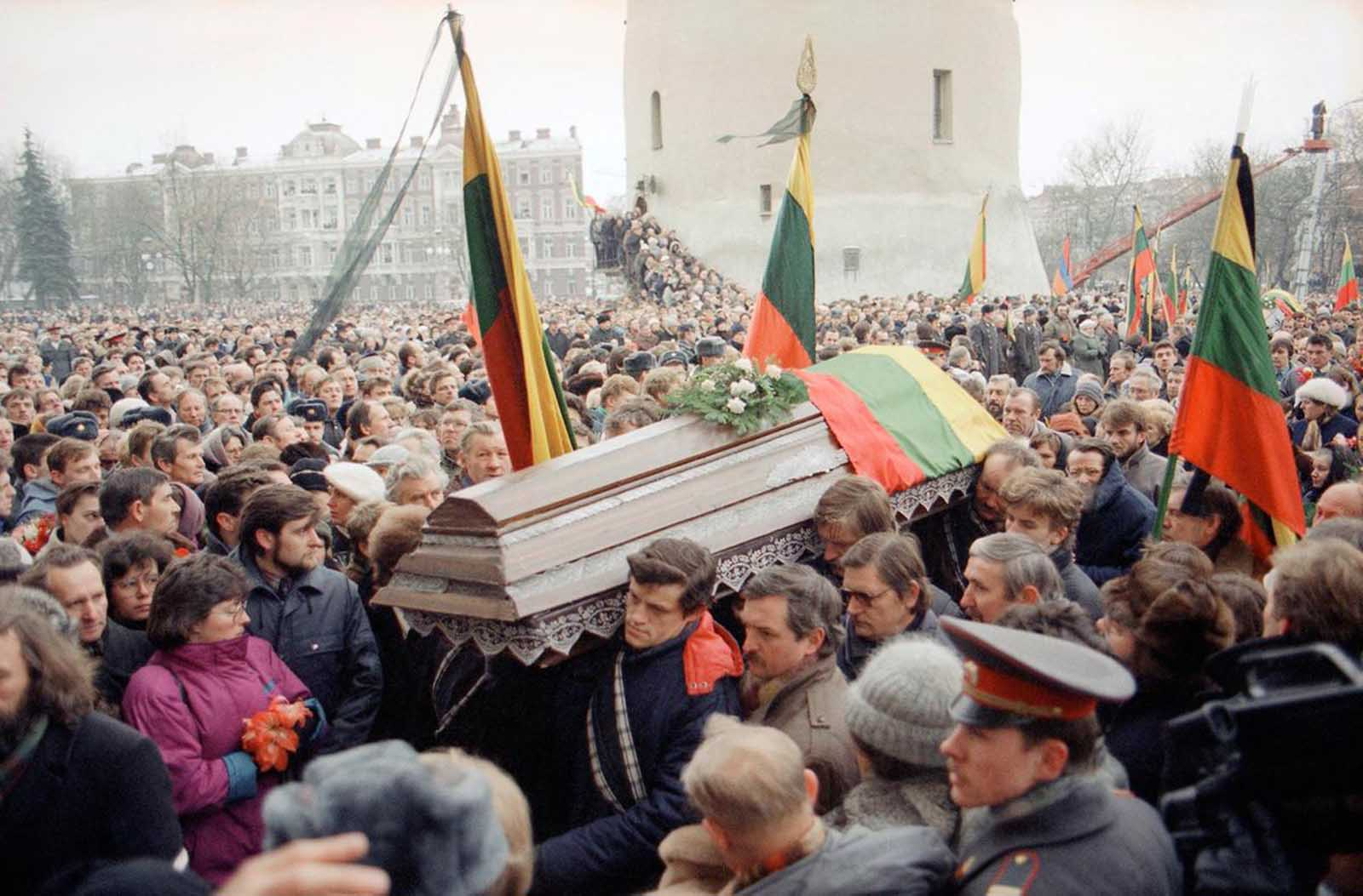 Pall-bearers carry a flag-draped casket during a funeral procession through Vilnius, on January 16, 1991, for 10 of the 13 people killed when Soviet troops stormed the Lithuanian broadcast center the previous weekend. Hundreds of thousands of Lithuanians jammed the procession route to mourn their national heroes.