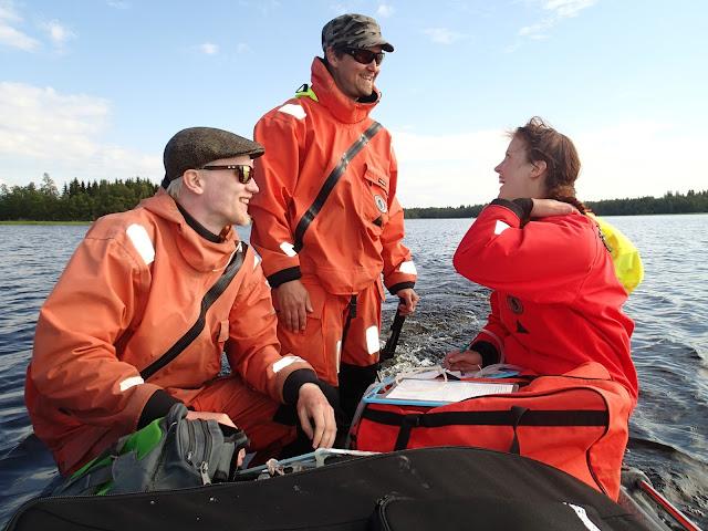 Kolme pelastautumispukuista kumiveneessä