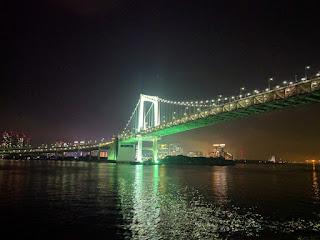 夜の船上から眺めるライトアップされたレインボーブリッジ