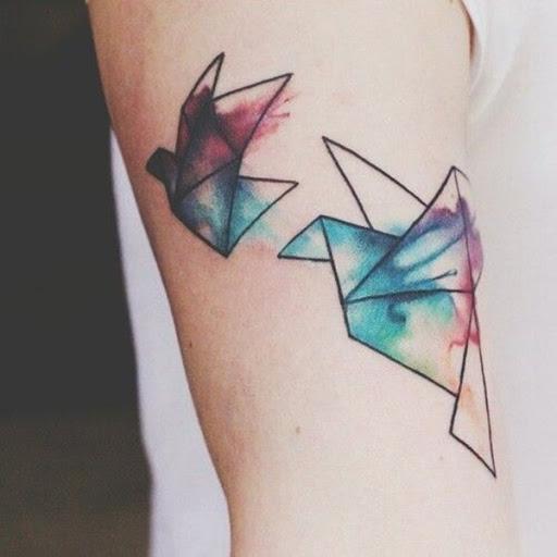 Um par de origami guindastes são acentuados com manchas de aquarela neste tatuagem conjunto representado o portador da parte superior do braço.