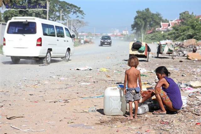 A woman washes dishes with her son on the side of a dirt road in Phnom Penh's Daun Penh district in 2013. Hong Menea