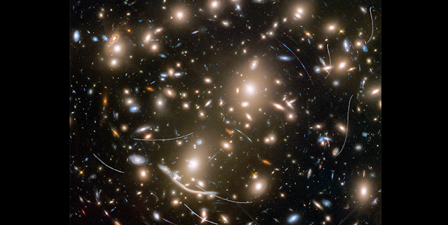 Galaxy cluster Abell 370 contains several hundred galaxies tied together by the mutual pull of gravity. It is located approximately 4 billion light-years away in the constellation Cetus, the Sea Monster. The thin, white trails that look like curved or S-shaped streaks are from asteroids that reside, on average, only about 160 million miles from Earth. The trails appear in multiple Hubble exposures that have been combined into one image. Of the 22 total asteroid sightings for this field, five are unique objects. These asteroids are so faint that they were not previously identified. Credits: NASA, ESA, and STScI
