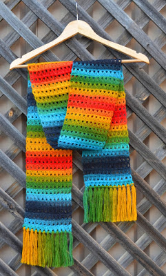 The broomstick lace rainbow scarf is hanging on a wooden coathanger against a wooden trellis.