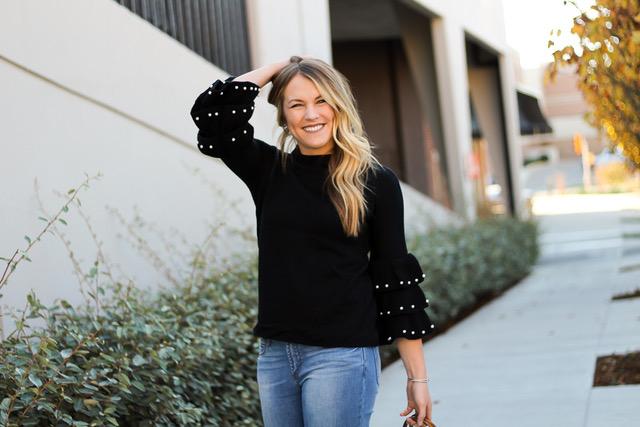 smiling girl wearing ruffle sleeve sweater