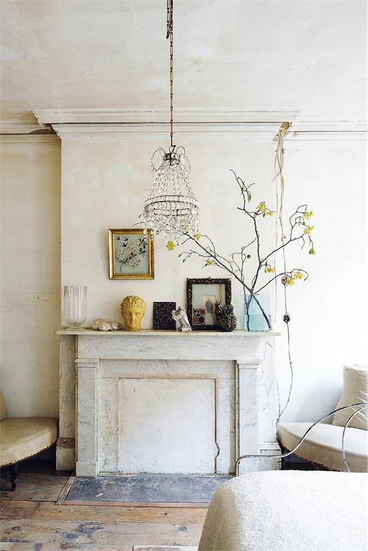 chimenea en el dormitorio con lampara de araña chicanddeco