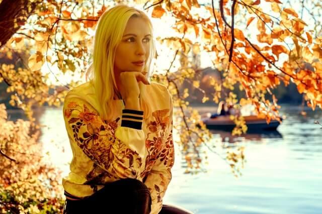 Woman Sitting Under Orange Leaf Tree Near River Bank HD Copyright Free Image