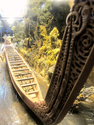 One-twelfth-scale diorama of a maori waka (war canoe) at the edge of a river.