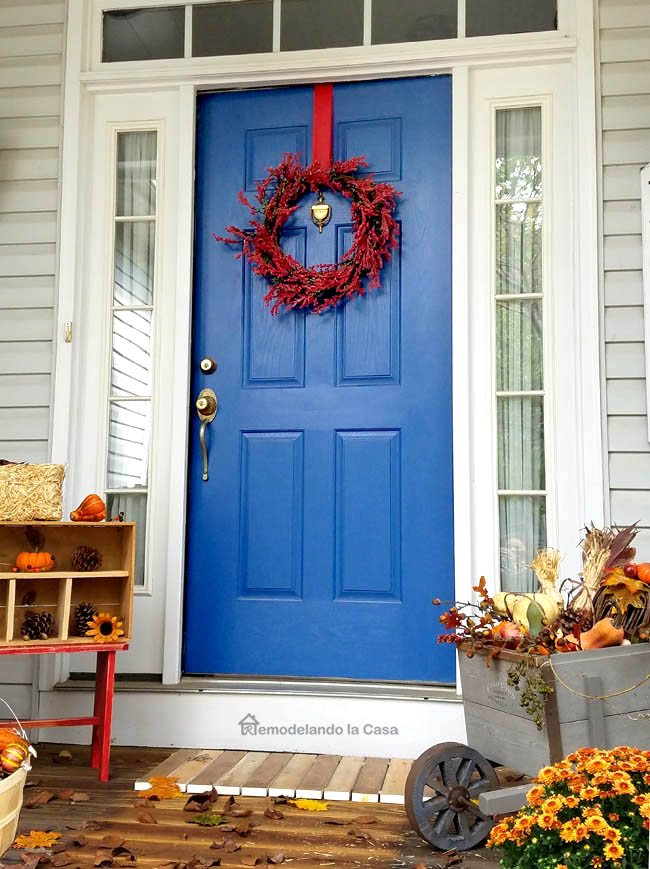 diy wooden wheelbarrow full of fall goodies, wooden doormat, mums, pinecone stand, blue door