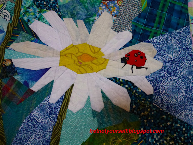 Detail of ladybug on daisy quilt