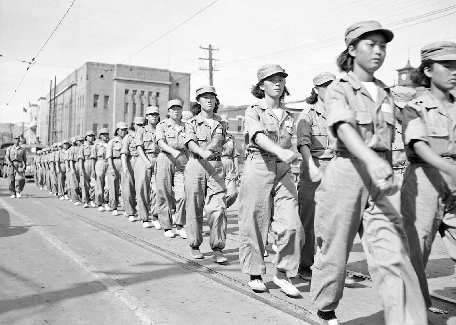South Korean WACs trained and ready to join their men in the battle against Chinese invaders, display military precision as they parade through Pusan, main United Nations' fort city in Korea, on September 12, 1950.